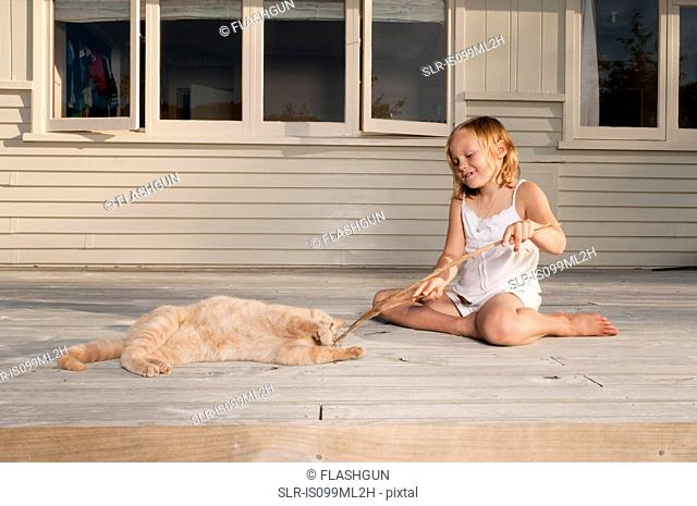 Girl and pet cat playing with stick