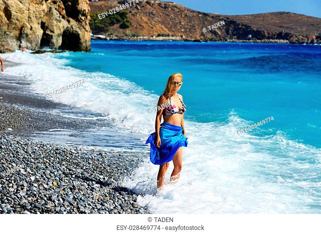Young woman on shore of blue sea