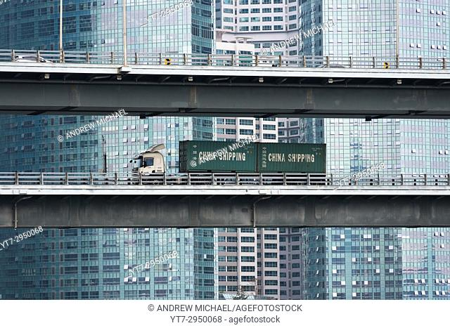 A Chinese lorry goes past the modern glass skyscrapers of Centum City, Pusan, South Korea
