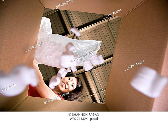 Woman putting packing peanuts in box