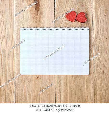 open notebook with a cell with empty sheets and red heart on a wooden background of oak boards