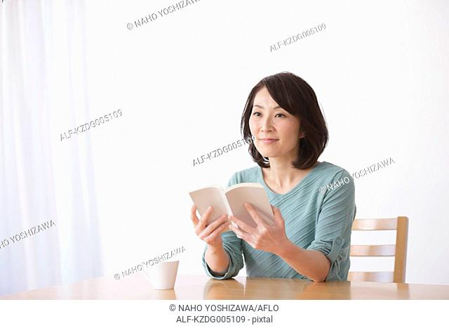 Senior Japanese woman with book in the living room