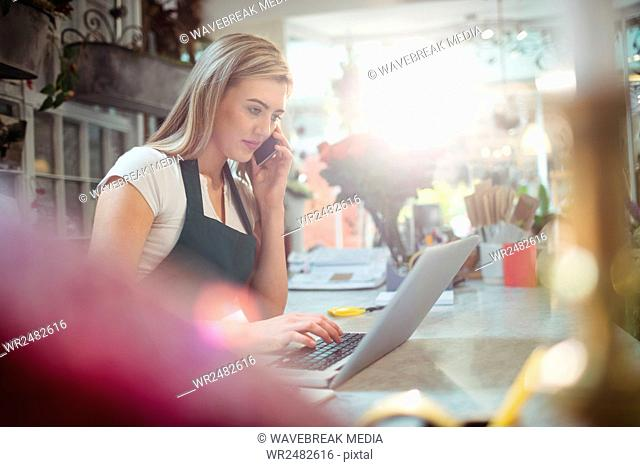 Female florist using laptop while talking on mobile phone