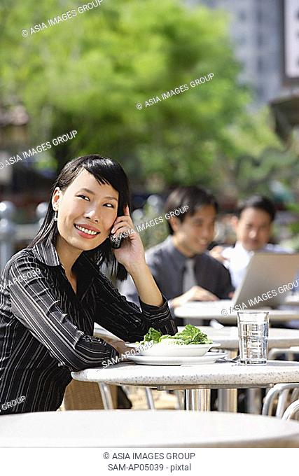 Businesswoman using mobile phone at outdoor cafe, people in the background
