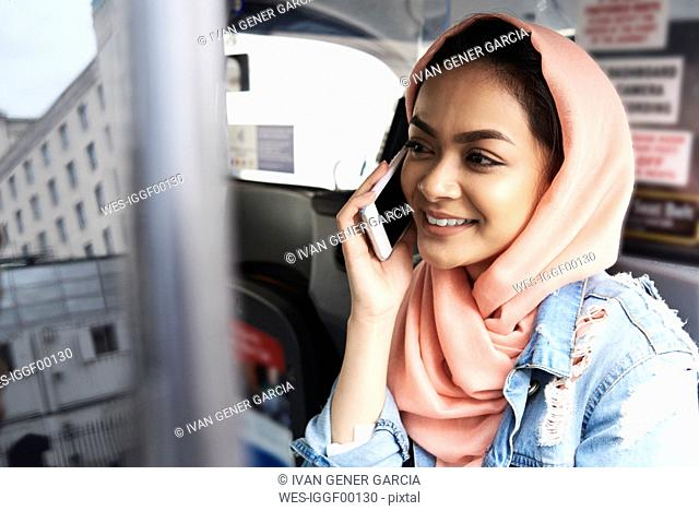 UK, England, London, young woman wearing hijab on the phone in a taxi