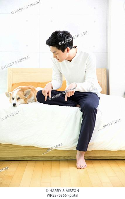 Young bachelor talking to his pet dog