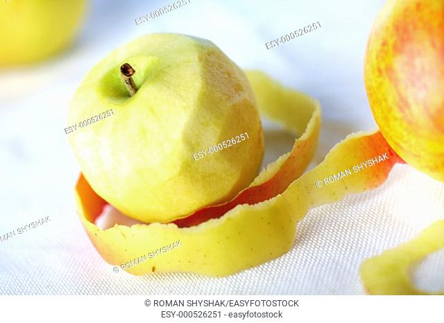 Yellow apple with peeled twisted skin against other apples