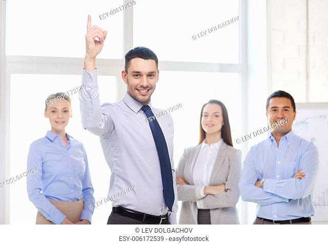 business and office concept - smiling handsome businessman with team in office and finger up