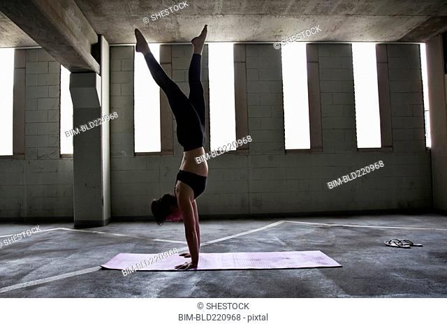Caucasian woman practicing yoga in parking lot