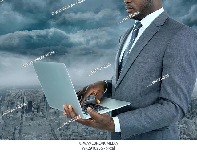 Businessman on laptop with city background