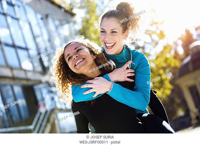 Happy young woman carrying friend piggyback