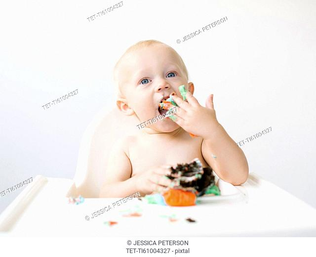 Baby boy (12-17 months) sitting in high chair and eating cupcake