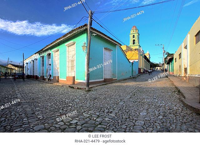 View along cobbled streets towards the bell tower of the Inglesia y Convento de San Francisco, Trinidad, Cuba, West Indies, Central America