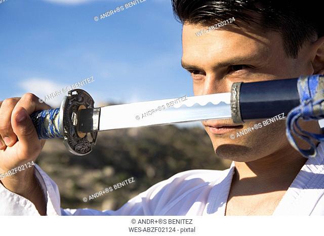 Man with defiant eyes drawing his katana sword