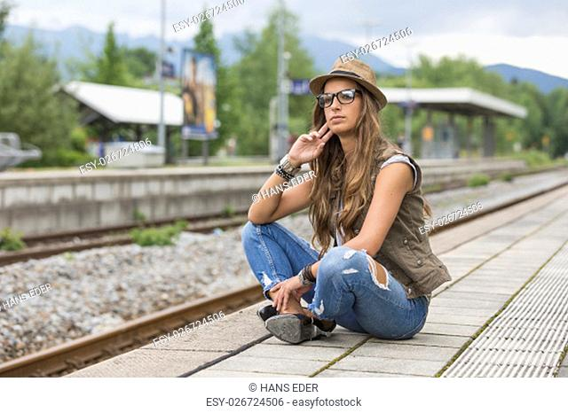 young woman waiting on a platform for their train