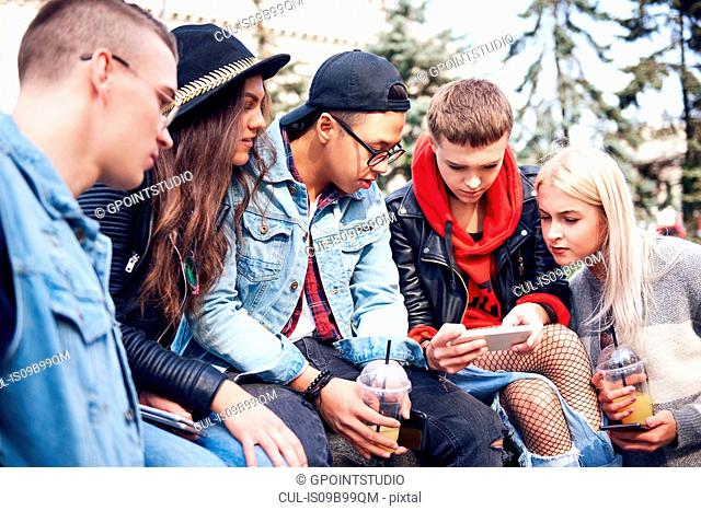 Five young adult friends sitting on wall looking at smartphone in city
