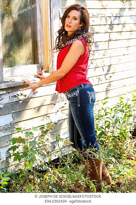 36 year old brunette woman with a somber expression looking directly at the camera, standing next to an old house, outdoors