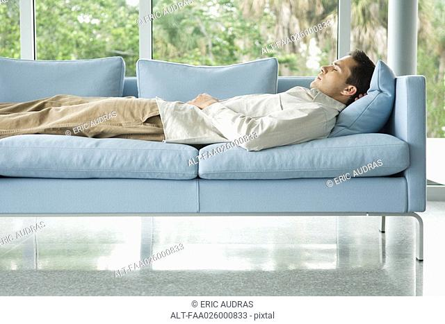Man lying on couch with hand behind head, eyes closed, side view