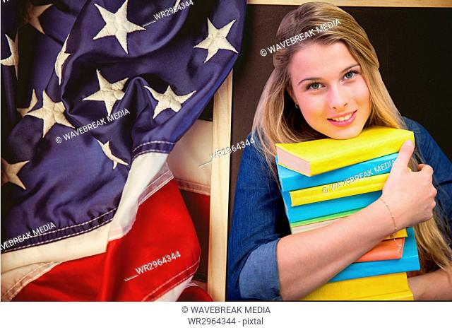 students holding books against american flag background