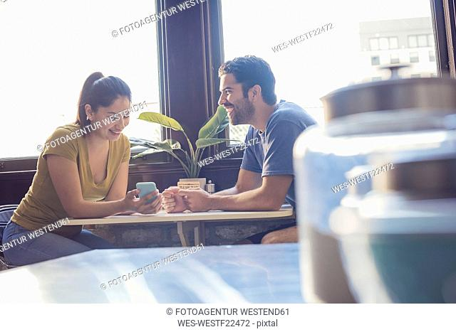 Young couple in kitchen using smart phone