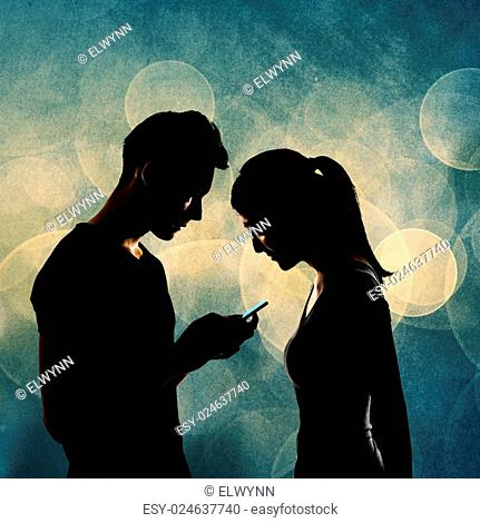 Couple using cellphone, silhouette portrait