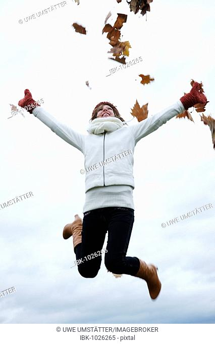 Female teenager wearing a hat and a scarf jumping in the air