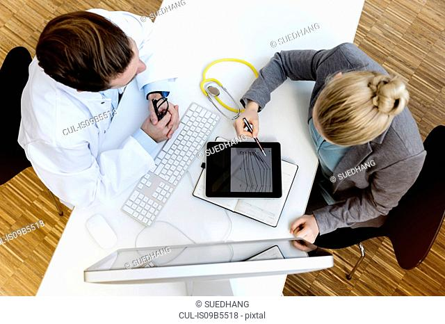 Doctor in meeting with consultant, overhead view