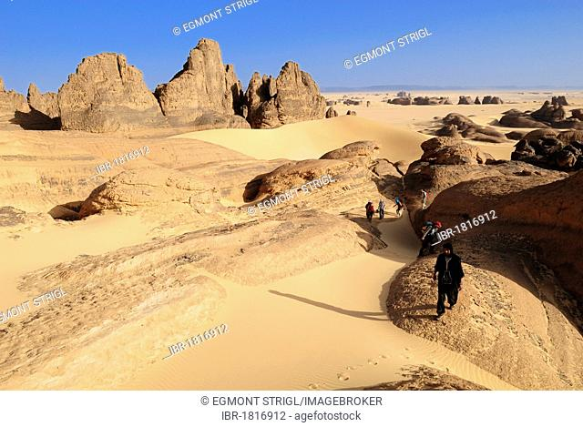 Group of tourists, hikers in the sandstone rock formation of Tin Akachaker, Tassili du Hoggar, Wilaya Tamanrasset, Algeria, Sahara desert, North Africa