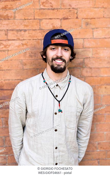 Portrait of relaxed young man wearing basecap and necklace