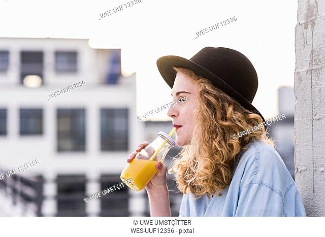 Portrait of young woman with hat drinking beverage
