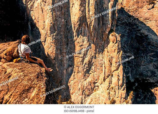 Rock climber on Higher Cathedral Spire looking away at view, Yosemite Valley, California, United States
