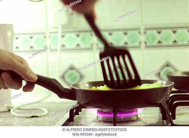 Person using frying pan