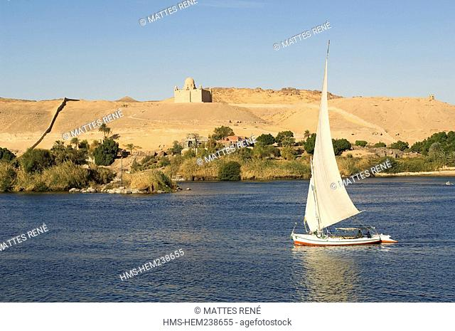 Egypt, Upper Egypt, Nubia, Nile Valley, Aswan, feluccas on Nile River, Aga Khan Mausoleum in the background in the left bank