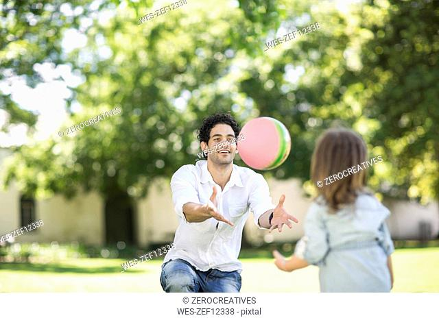 Father playing ball in garden with daughter