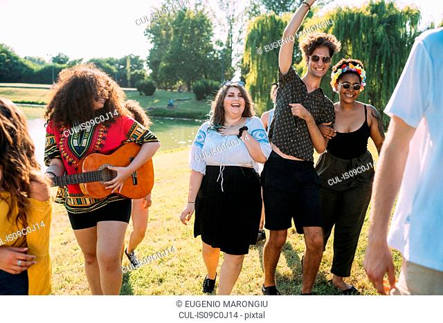 Group of friends dancing, playing guitar in park