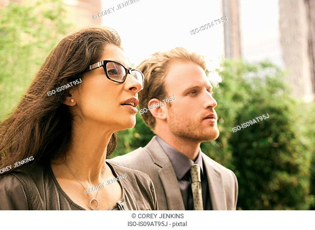 Businessman and woman in city staring