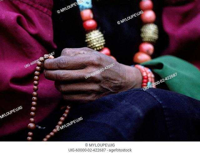 DOLPO WOMAN counts beads on her BUDDHIST ROSARY and wears a CORAL, TURQUOISE and GOLD NECKLACE - DOLPO DISTRICT, NEPAL