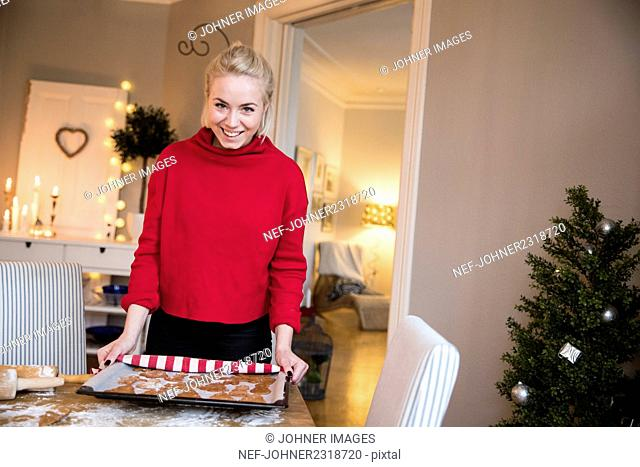 Young woman baking gingerbread cookies