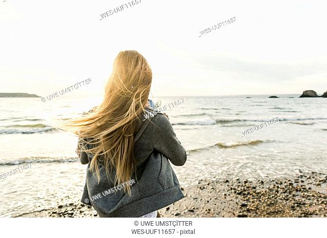 Young woman watching the sunset on the beach