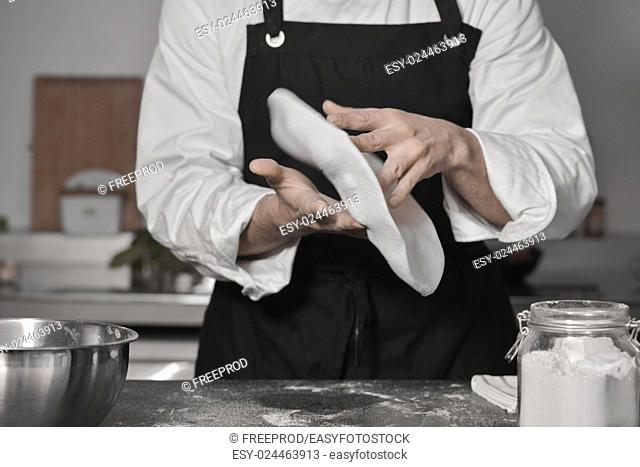 Chef cooking pizza in kitchen with hands
