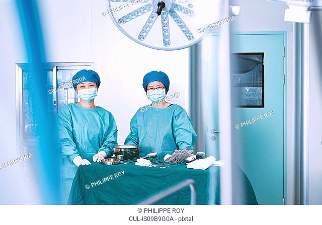 Portrait of two female surgeons in maternity ward operating theatre