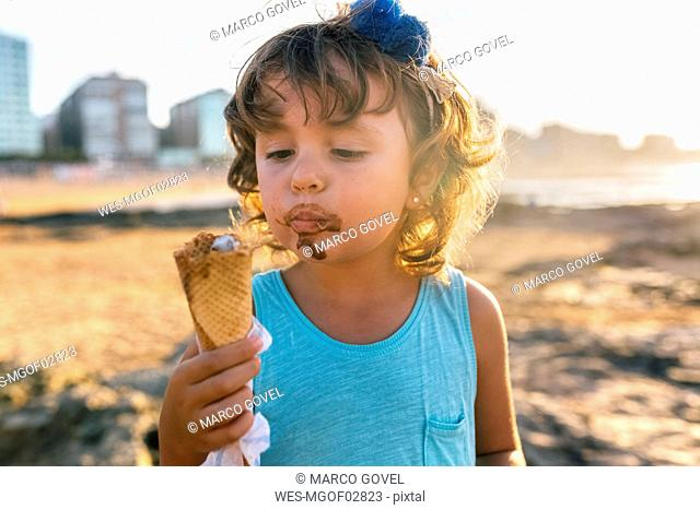 Portrait of little girl eating chocolate icecream on the beach at sunset