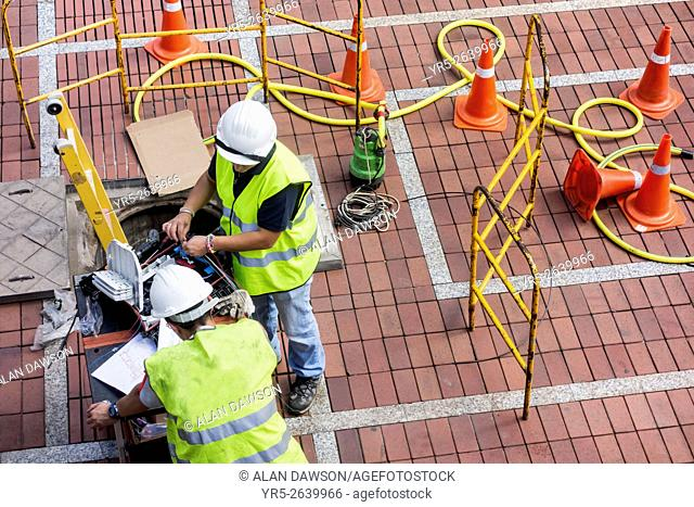 Telephone engineers (male and female) working in city street in Las Palmas, Gran Canaria, Canary Islands, Spain