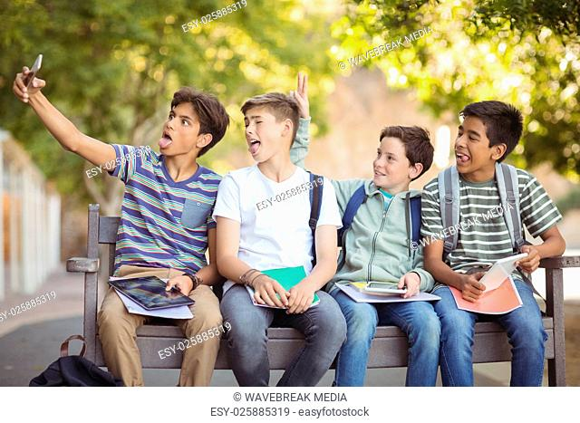 Happy students sitting on bench and taking selfie on mobile phone