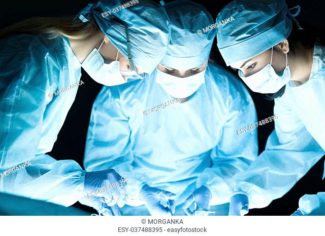 Medical team performing operation. Group of surgeon at work in operating theatre