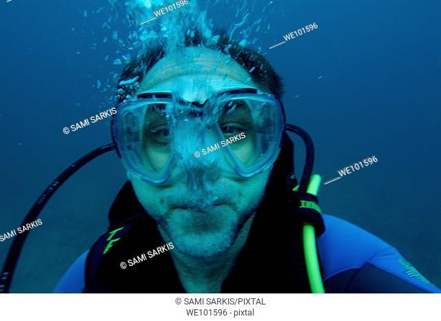 Scuba diver expiring air without his regulator near the Ari Atoll, Maldive Islands