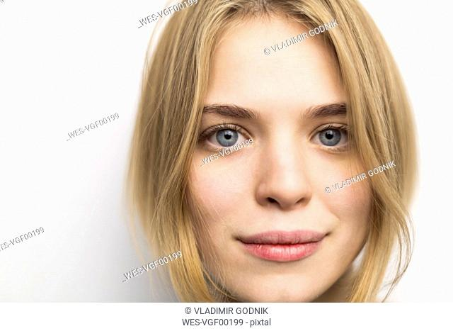 Portrait of blond young woman against white background