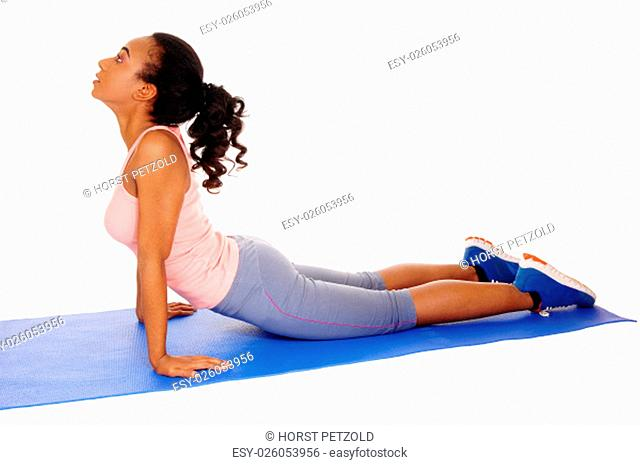 A young African American girl lying on a yoga mat, stretching her body, .in blue tights, isolated for white background.