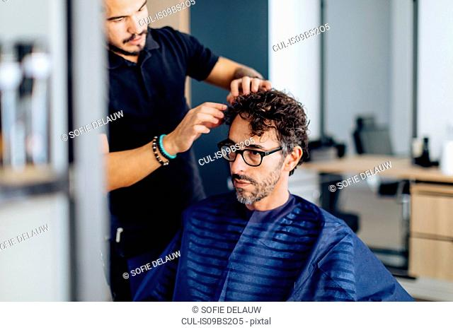 Male hairstylist styling male customer's hair in hair salon