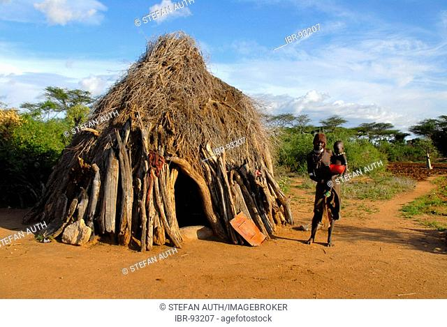 Mother with baby on her arm of the Hamar people in front of typical hut in the savannah near Turmi Ethiopia
